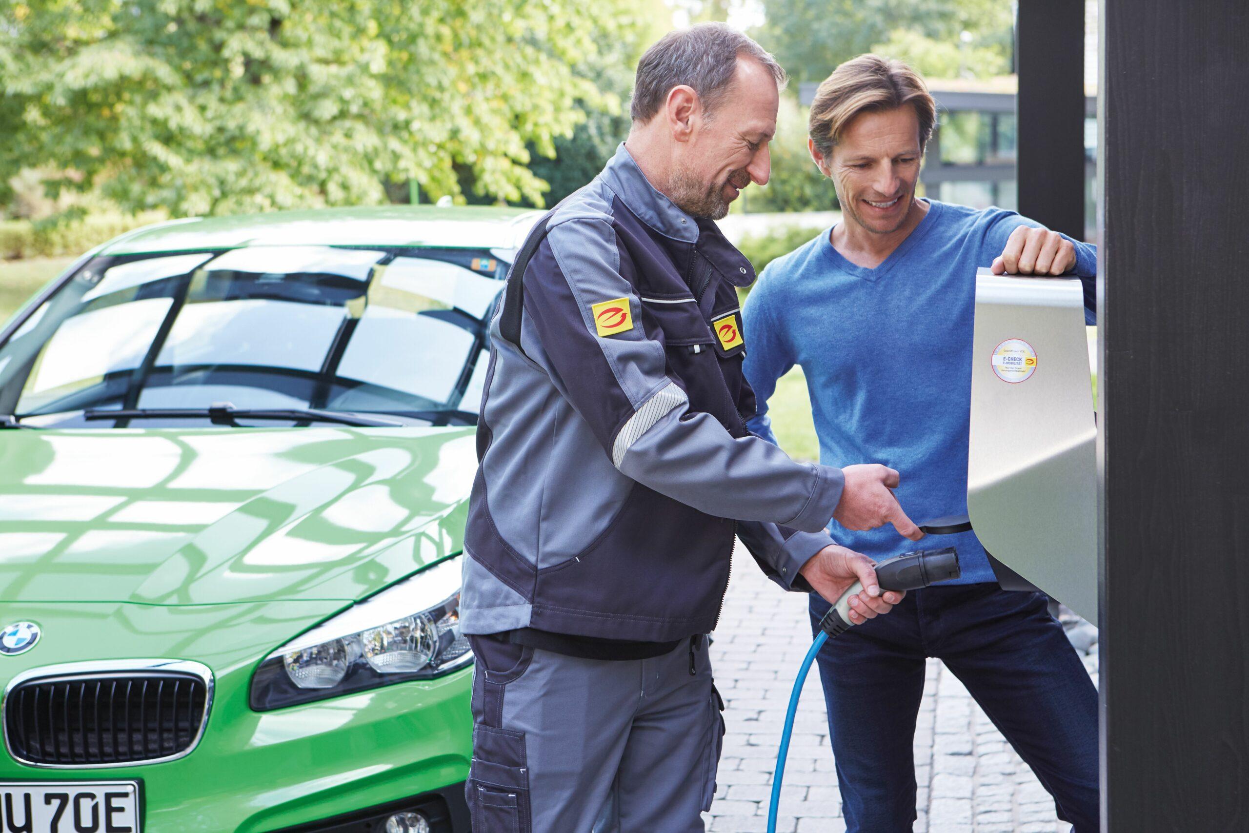 Elektrofachmann erklärt dem Kunden die E-Ladestation